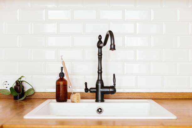 Küche mit weißem Waschbecken und schwarzem Wasserhahn Holzarbeitsplatte – Foto