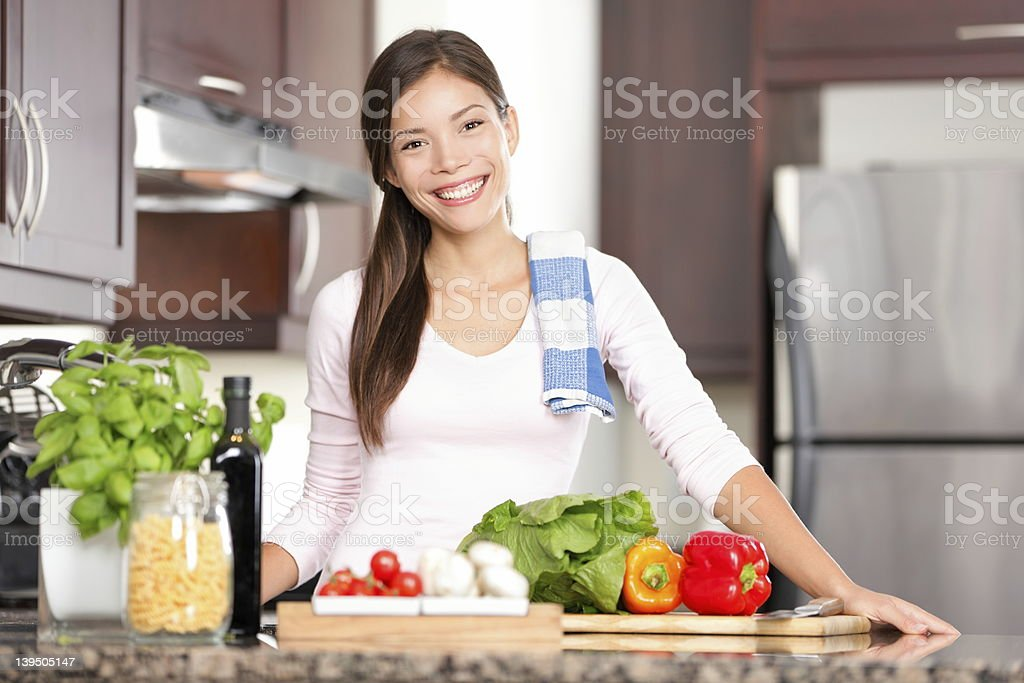 Kitchen woman making food kitchen woman making healthy food standing happy smiling in kitchen preparing salad. Beautiful cheerful multicultural Chinese Asian / Caucasian young woman at home. See more: 20-29 Years Stock Photo