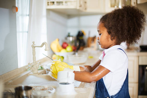 Kitchen work Little girl washing dishes in the kitchen chores stock pictures, royalty-free photos & images
