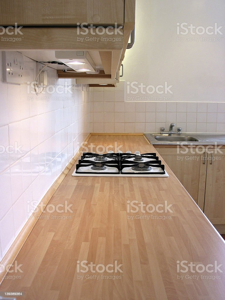 Kitchen worktop with recessed gas hobs and cupboards overhead stock photo