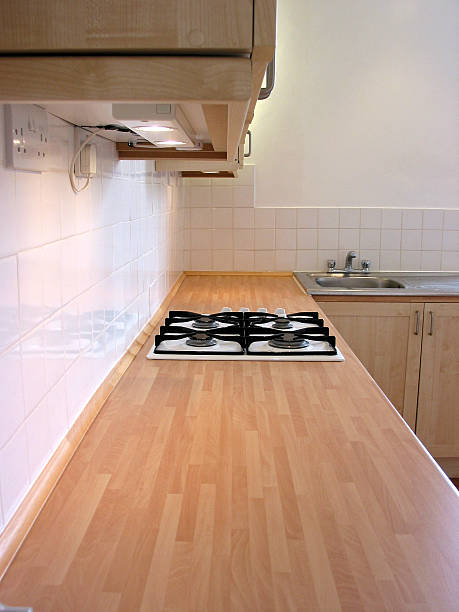 küche arbeitsfläche mit eingearbeiteten gas hobs und schränken über - laminatschränke stock-fotos und bilder