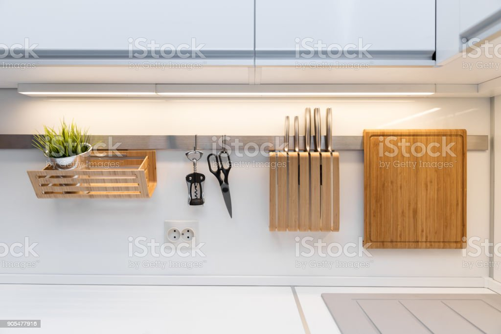 kitchenware hanging on the rail in the white glossy kitchen stock photo