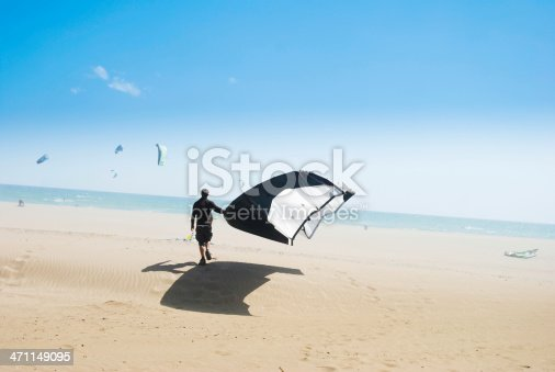 Man carrying his sail to the shoreline.