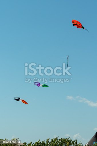 Reflection of colorful kite against blue sky with white clouds