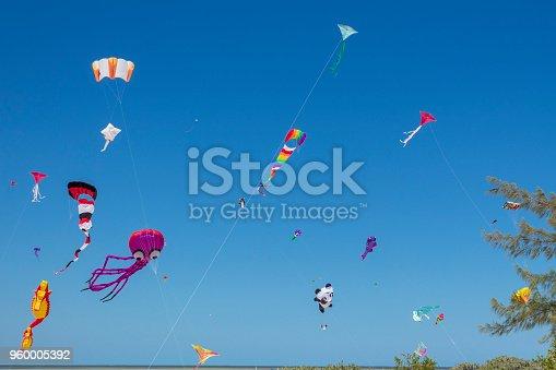 Colorful, creative kites fly against a deep blue sky in the caribbean
