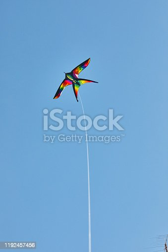 Kite flying on a rope in the blue sky on a bright sunny day.