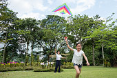 Young girl and her grandfather flying a kite at the park