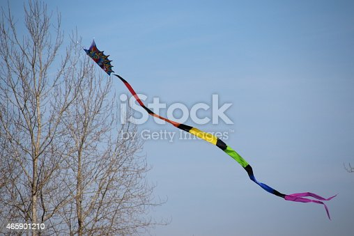 Multi colored kite flying high in the sky.