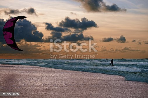 Kite surfer is surfing along the beach in beautiful sunset.