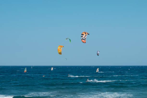 kitesurfer und windsurfer am meer am strand von el medano - kitesurfen lernen stock-fotos und bilder