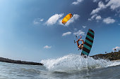 Kite surfer with wakeboard jumps against blue sky. Water extreme sports concept