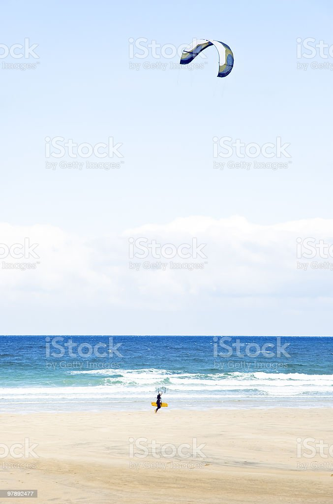 kite surfer walking along beach. royalty-free stock photo