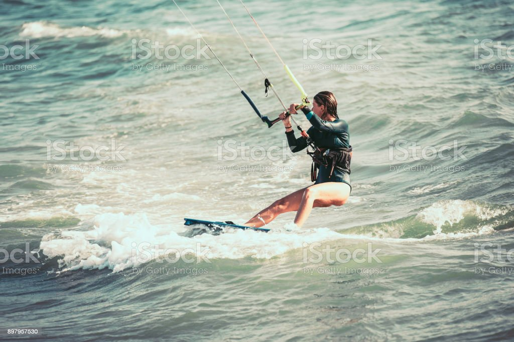 Kite surfing girl riding waves stock photo