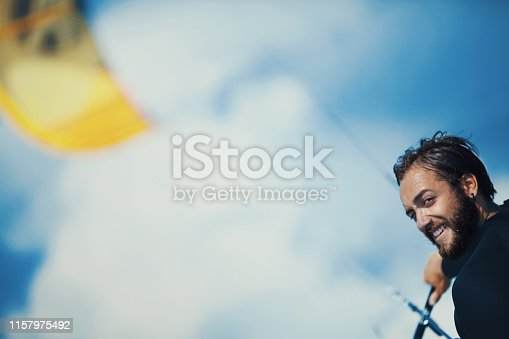 Side view of young man kite surfing. He's smiling and looking at camera over the shoulder.