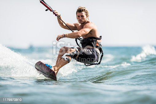 Muscular build man surfing on kiteboard during summer day at sea. Copy space.