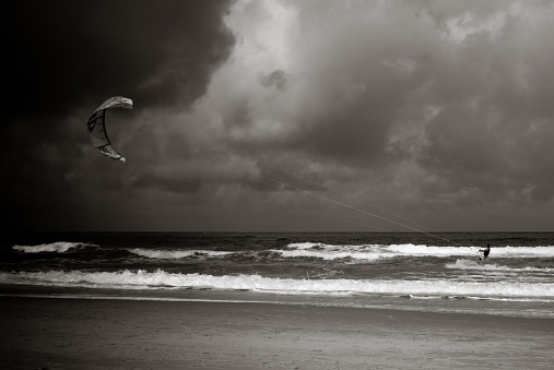 Kiteboarder riding in as a storm blows in