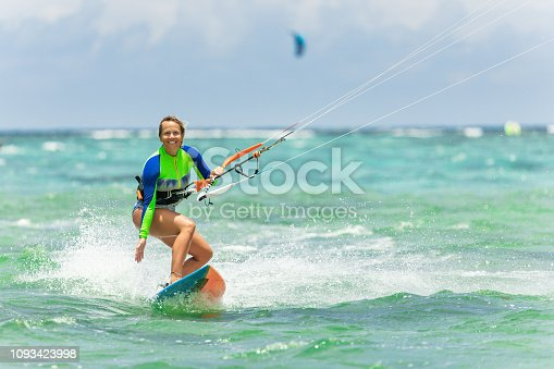Girl kiteboarding in beautiful water of Mauritius.  Waves in background and kite is low.
