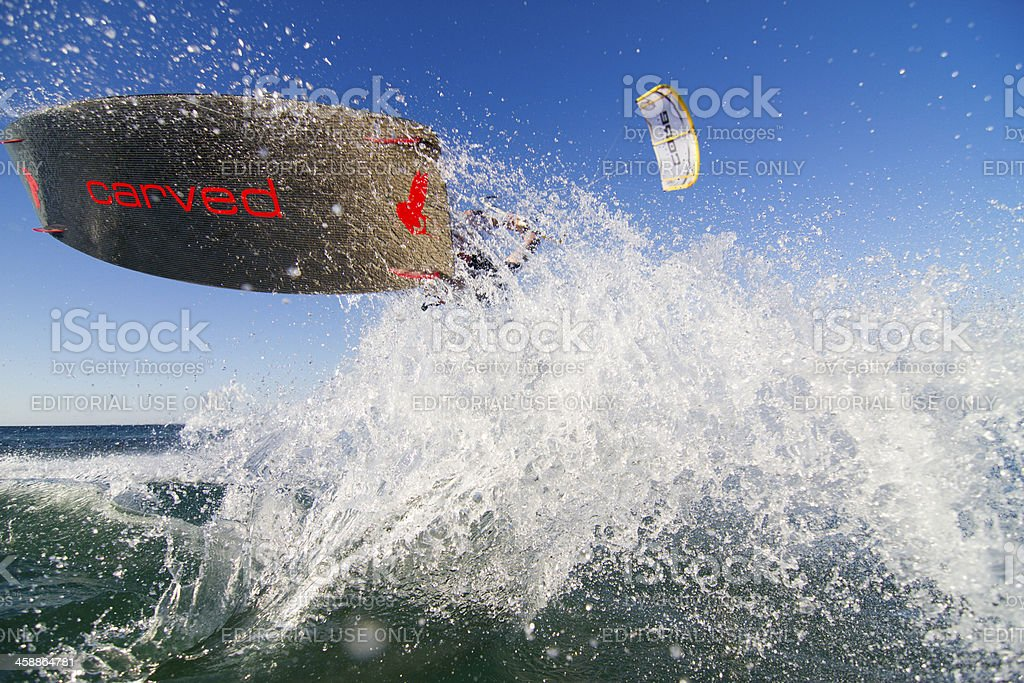 Kiteboarding jump with much spray and kite in background stock photo