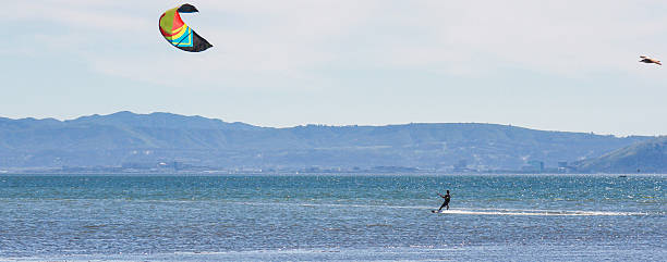 Kiteboarding, kitesurfing stock image color landscape photo of a single kiteboarder surfing in the ocean. hills in background, blue sky. alameda california stock pictures, royalty-free photos & images