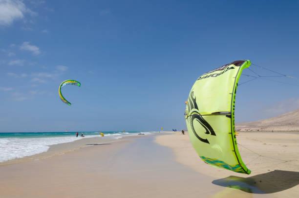 drachen in den himmel über sotavento strand, fuereventura, kanarische inseln - kitesurfen lernen stock-fotos und bilder