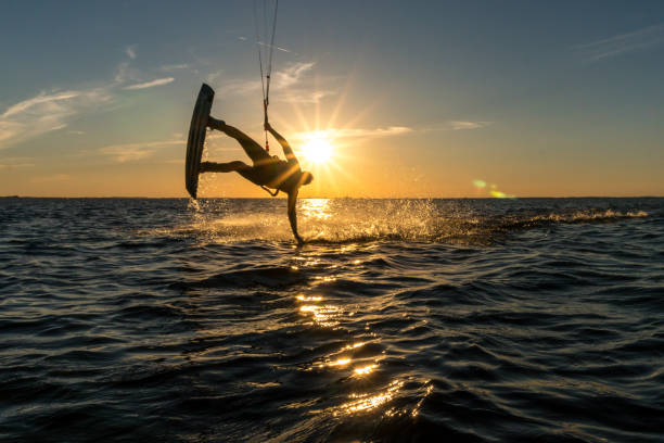 kitesurfer doing handslide in sunset with sunstar and beautiful silhouette kitesurfer doing handslide in sunset with sunstar and beautiful silhouette wasser photos stock pictures, royalty-free photos & images