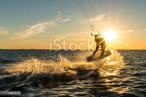 kitesurfer doing tricks in sunset