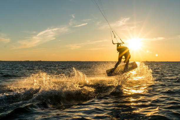 kitesurfer doing tricks in sunset - wasser stock pictures, royalty-free photos & images