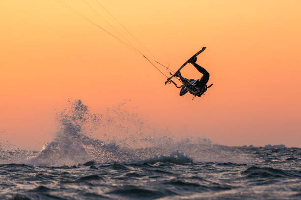 Kitesurfer doing unhooked tricks in beautiful sunset conditions and nice colors Kitesurfer doing unhooked tricks in beautiful sunset conditions and nice colors wasser photos stock pictures, royalty-free photos & images