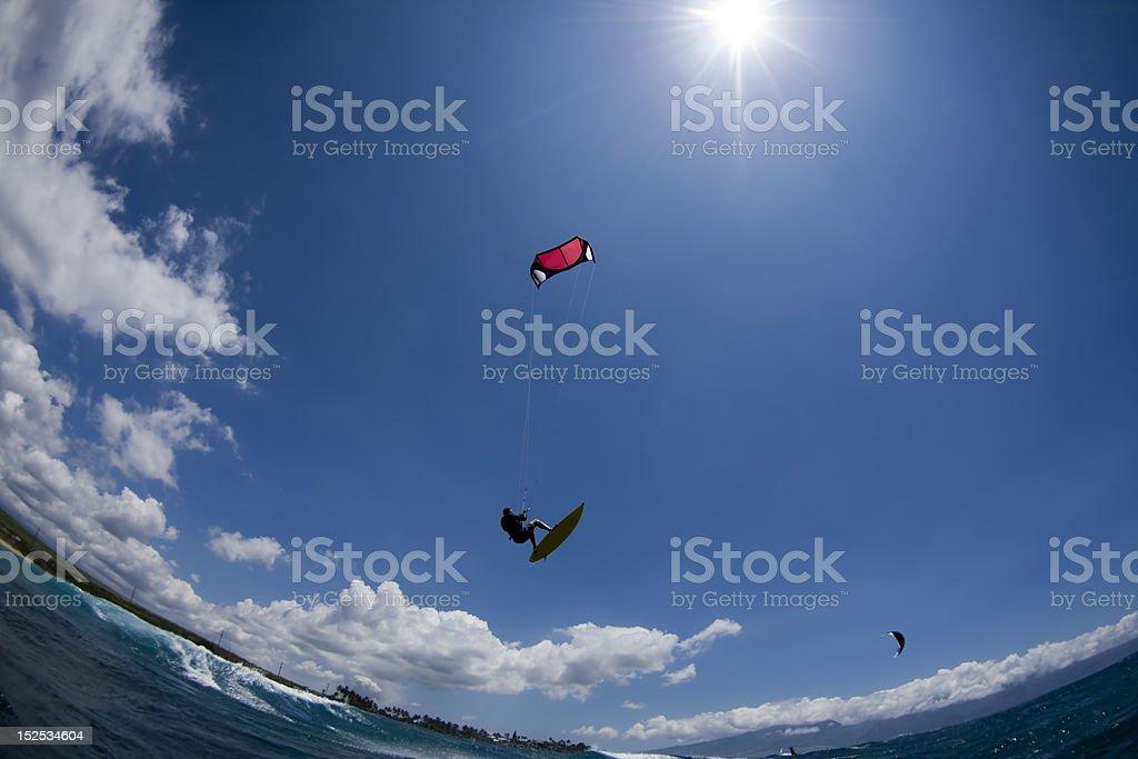 Kitesurfer Flying Through Blue Sky stock photo