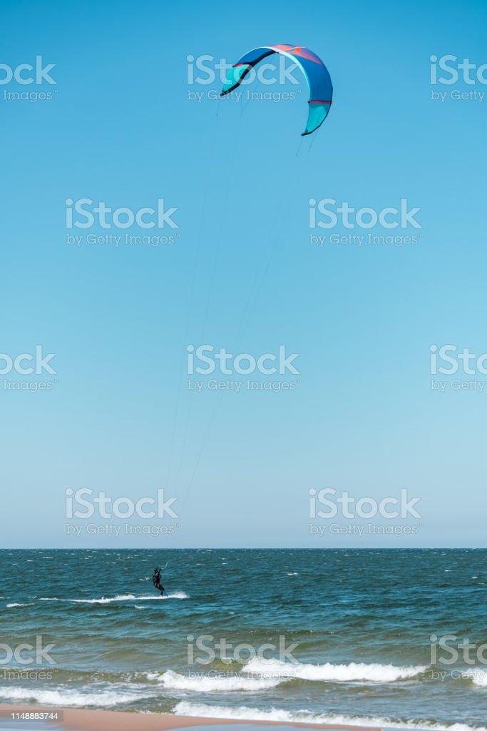 Kitesurfer swimming on an ocean or sea near beach. stock photo