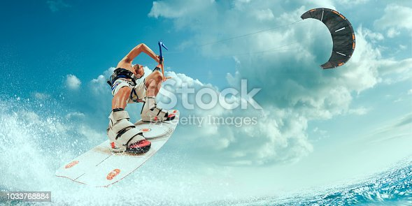 Kitesurfing. Man rides a kite on wave