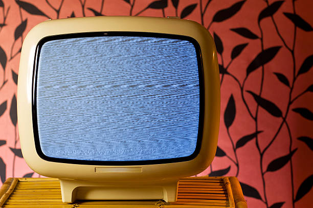 Kitschy retro style TV in front of pink floral wallpaper Retro grunge tv against wallpaper wall..White noise on television. portable television stock pictures, royalty-free photos & images