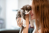 Woman holding up a kitten and smiling, cuddling her.