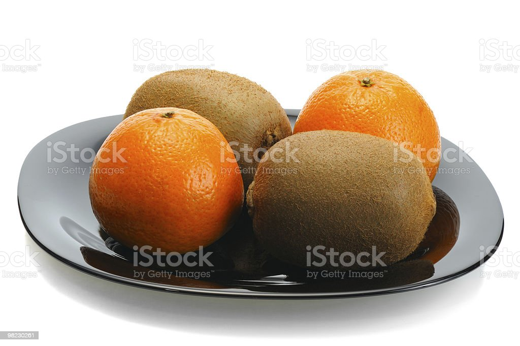 Kiwi and mandarin on a black plate royalty-free stock photo