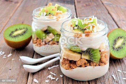 istock Kiwi, banana, coconut parfaits in mason jars on rustic wood 641395480