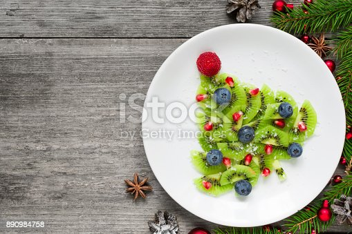 istock kiwi christmas tree with berries, pomegranate seeds and coconut looks like snow. funny food idea for kids 890984758