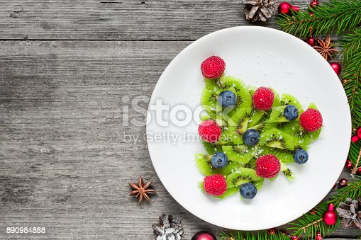 istock kiwi christmas tree with fir tree branches over rustic wooden table. funny food idea for kids 890984888