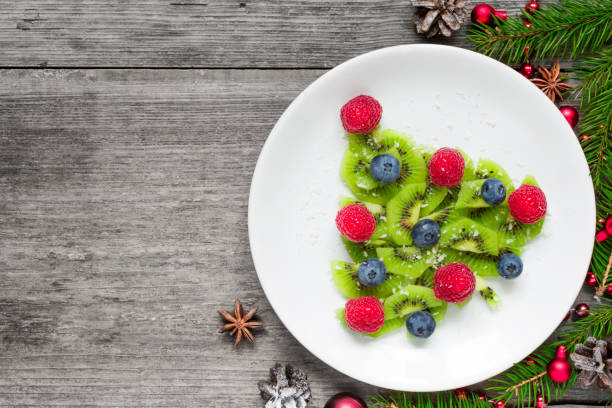 kiwi-weihnachtsbaum mit tanne äste über rustikalen holztisch. lustig essen idee für kinder - weihnachtsessen ideen stock-fotos und bilder