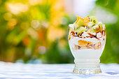 キウイ トウモロコシはフレークと野菜草カップ、ペーパー ノート、鉛筆、庭で休日ピクニック ヨーグルトのフォーカスを選択します。