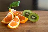 Kiwi fruit and an orange on dark table.