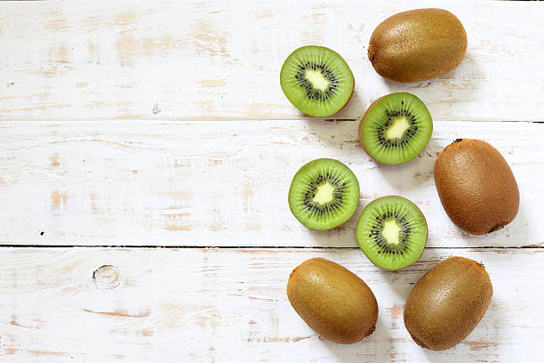 kiwi fruit on white wooden background - 奇異果 個照片及圖片檔