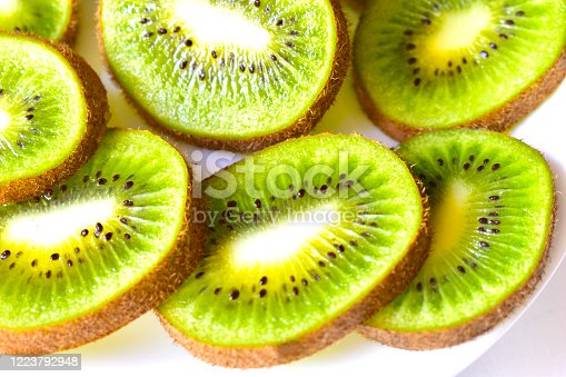 Kiwi fruit sliced on a snow white plate