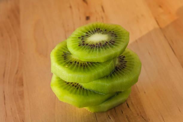 kiwi fruchtscheiben auf einem holztisch - alvarez stock-fotos und bilder