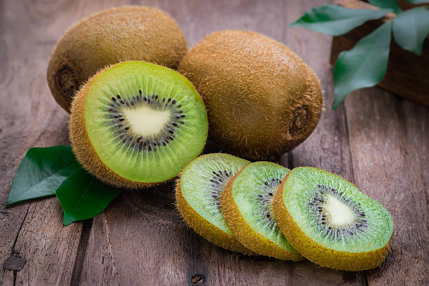 kiwi fruit slices on wooden table - 奇異果 個照片及圖片檔