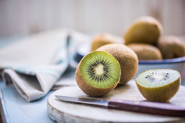 kiwi halves on wooden board - kiwi imagens e fotografias de stock