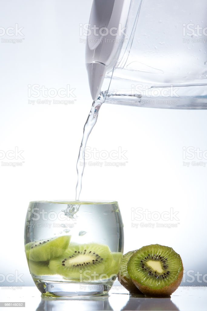 Kiwi in a glass and splashes of water. Tasty and healthy food....