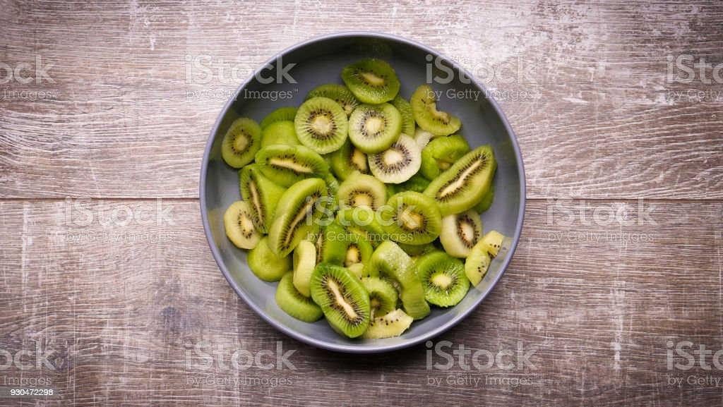 kiwi in a plate on a wooden background stock photo