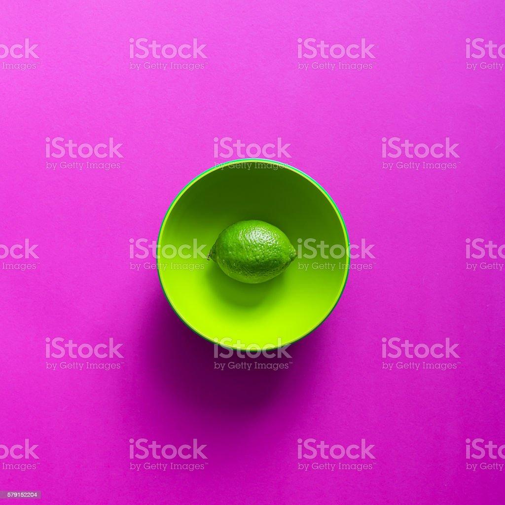 Kiwi in green bowl on purple background. royalty-free stock photo