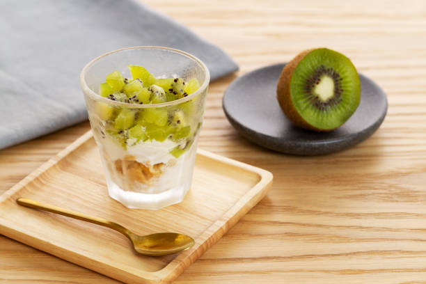Kiwi parfait dessert with kiwi fruit, yogurt and crumble in a wooden plate over a wooden background. stock photo