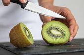 A woman cutting kiwi.